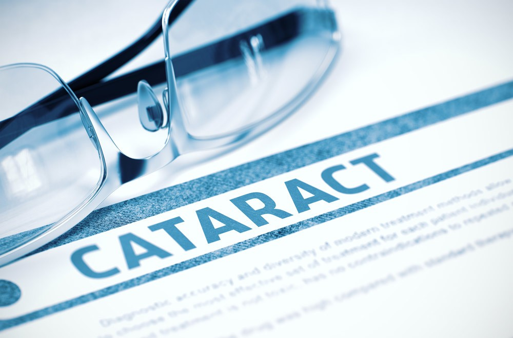 "pair of eye glasses on a piece of paper that reads ""cataract"""