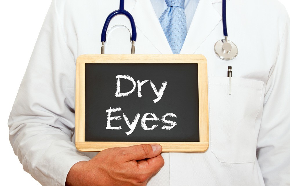 "Physician holding small chalk board that reads ""dry eyes""."